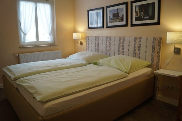 Das komfortable Doppelbett mit zwei getrennten Matratzen und hoher Einstiegshöhe in einem großzügigen Schlafzimmer.