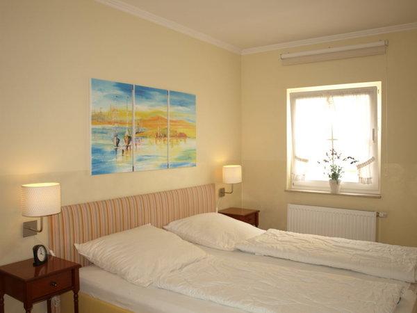 Das Schlafzimmer mit großem Bett mit zwei Matratzen und hoher Einstiegshöhe und zweitem Flachbildfernseher
