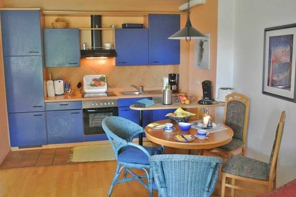 komplett eingerichtete Küchenzeile mit Esstisch im Vordergrund