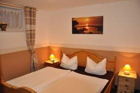 Blick in das kleine Schlafzimmer mit massivem Doppelbett und kleinem Lüftungsfenster. Angenehm kühles Raumklima im Sommer.
