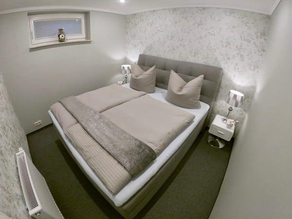 Blick in das kleine Schlafzimmer mit großem Boxspringbett und kleinem Lüftungsfenster. Angenehm kühles Raumklima im Sommer.