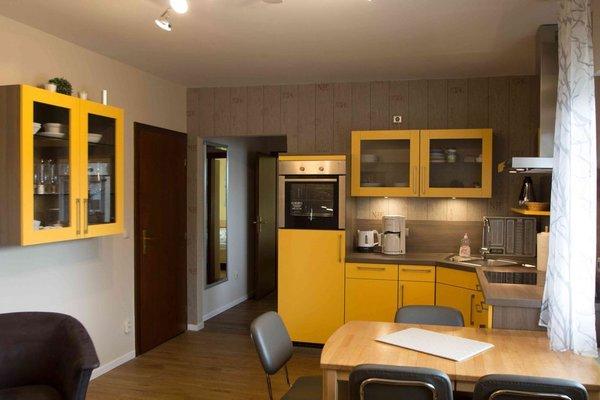 Ansicht Küchenzeile mit Spülmaschine, Backofen und Essbereich im Wohnzimmer