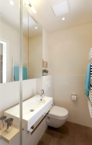 Beide Bäder sind mit einer Echtglas-Dusche, bodengleicher Duschtasse, Handbrause, zusätzlicher Regenbrause und großzügigen Spiegelschränken mit viel Stauraum, WC und einem Haarfön ausgestattet.