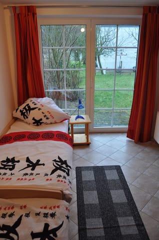 Zweites Schlafzimmer mit zwei Betten, Schrank und Stühlen