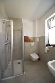 Tageslicht-Bad mit Dusche, WC, Waschbecken, Handtuchtrockner, Fön, Fußbodenheizung