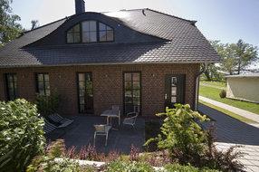 Terrasse mit Gartenmöbeln und Liegen, Zugang über die großen Fenstertüren