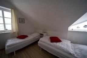 """Schlafraum 2 mit 2 Einzelbetten, 2 Fenstern mit Blick auf die Salzwiesen , die """"Zicker Alpen"""" und die Hagensche Wiek, Laminatboden"""