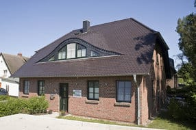 Grüne Wohnung von Außen mit Terrasse, die sich an der rechten Hausseite befindet und  sich auch noch hinter dem Haus fortsetzt