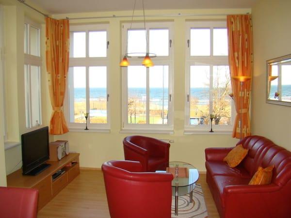Aus dem hellen Wohnzimmer mit Schlafcouch  blicken Sie auf die Promenade und direkt auf die Ostsee.