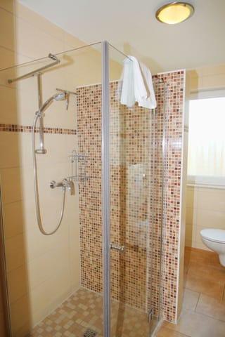 Bad mit ebenerdiger Dusche und Fenster