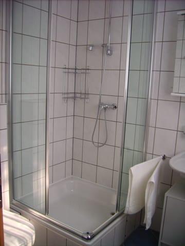 Im Badezimmer befindet sich ein WC, eine Dusche und ein Waschbecken. Das Bad hat ein eigenes Fenster.