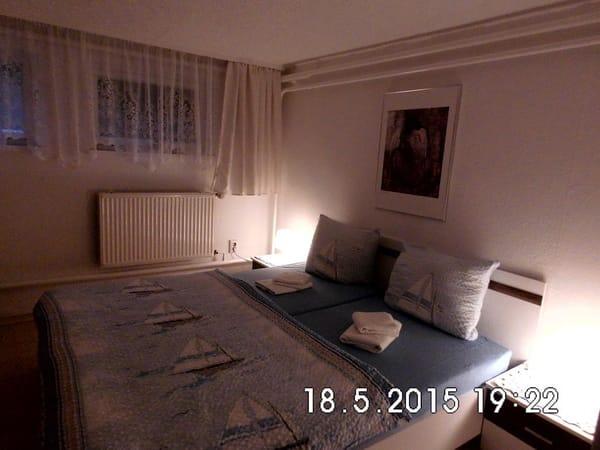 Schlafzimmer mit bequemen Doppelbett im Marinestil am Abend