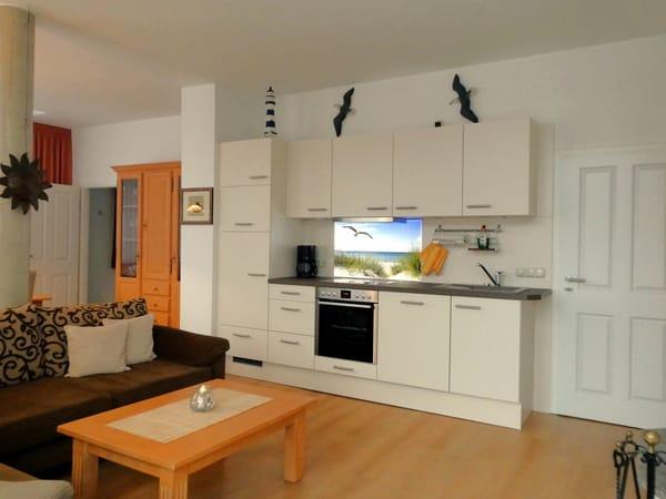 Aus Richtung des Balkons blicken Sie nun auf die komplett ausgestattete Küchenzeile. Links daneben beginnt der Essbereich