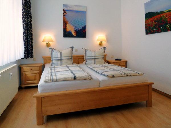 Das Schlafzimmer ist mit einem Doppelbett, 2 Nachttischen und einem 3türigen Kleiderschrank aus Kiefernholz ausgestattet.