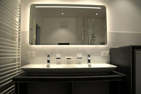 Das Badezimmer mit Handtuchheizung und Doppelwaschtisch.