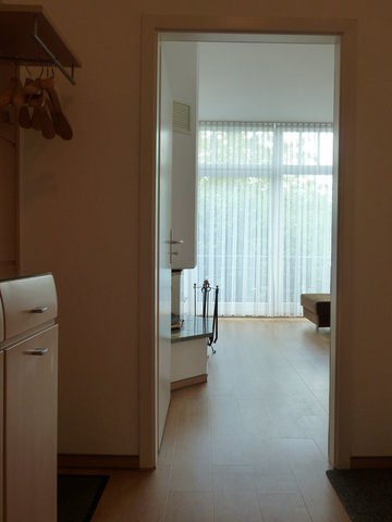 Treten Sie ein. Das Bild zeigt den Flur, die offene Tür zum Wohnzimmer und Blick zum Balkon. Rechts im Flur (auf diesem Bild nicht zu sehen) geht es in das Badezimmer.