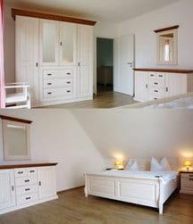 eines der freundlich eingerichteten Schlafzimmer mit großem Doppelbett und Kleiderschrank sowie einem Kinderbett