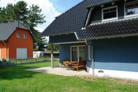der Blick von Ihrer Liegewiese zur Terrasse und dem Zugang zum Wohnraum