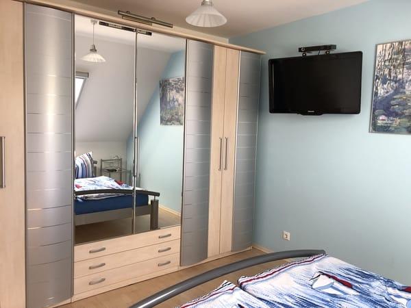 Blick ins Schlafzimmer zum großen Kleiderschrank und Flachbild-TV