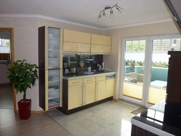 Küche mit Geschirrspüler, Kühlschrank, Induktionsherd mit  Backofen, Mikrowelle und Terrasse mit Rattanmöbeln