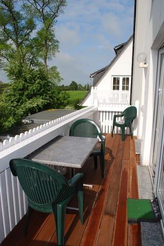 Der Sonnenbalkon -Südseite- mit Tisch und Stühlen
