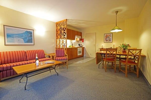 Wohnzimmer mit Schlafcouch, Esstisch und Küchenzeile