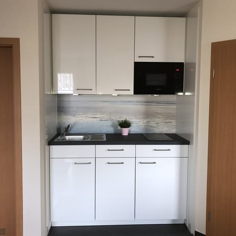 neue Küchenzeile mit Geschirrspüler, Kühlschrank, Mikrowelle und Ceranfeld