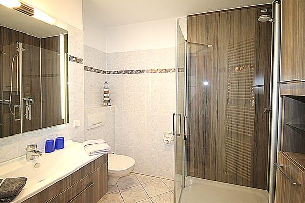 Helles Badezimmer mit WC, XL-Dusche,  Handtuchwärmer, Fön und viel Ablagefläche
