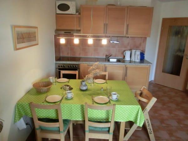 Eß- und Küchenbereich mit zusätzlich ausziehbarem Tisch und 5 Stühlen. Der auf dem Foto sichtbare Hochstuhl gehört zur Wohnung.
