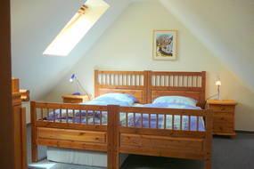 Oberes Schlafzimmer mit einem Doppel- und einem Einzelbett. Die Fenster sind mit Rollos zur Abdunkelung ausgestattet.