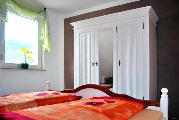 Schlafraum mit Doppelbett und großem Schrank