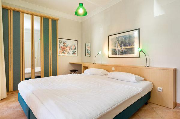 Das Schlafzimmer hat ein Doppelbett, einen großen Kleiderschrank ...