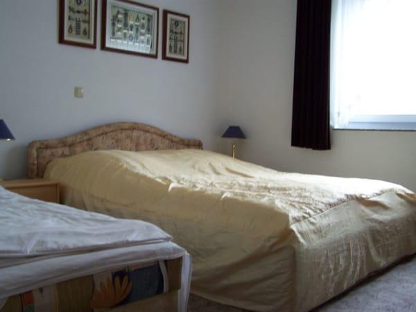 Schlafzimmer mit Doppelbett und separater Liege.