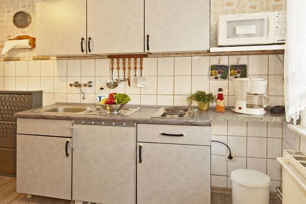 Der Küchentrakt  zum  kochen, kühlen, abwaschen,  mit Geschirr, Wasserkocher, Besteck, Kaffeemaschine, Mikrowelle.