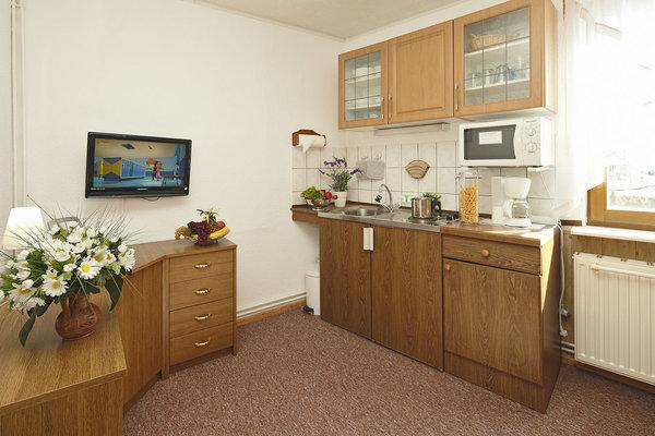 die komb. Wohnküche, mit Sideboard, komplette Kücheneinrichtung, TV,  Eine Sitzcouch, ein Sessel und Tisch