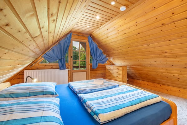 Schlafzimmer 1 hat ein Doppelbett und einen Austritt zum Balkon. Kinderreisebettchen und Hochstuhl werden gern bereit gestellt.