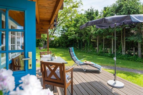 Die Terrasse ist komfortabel möbliert. Auch die Wiese am Haus kann als Liegewiese genutzt werden.