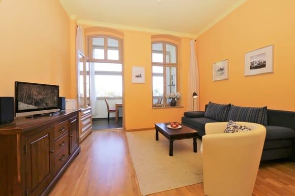 Wohnbereich mit Schlafcouch und  Zugang zur Loggia mit teilw. Ostseeblick
