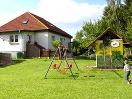 Der kleine Spielplatz verfügt über ein Spielhäuschen mit Rusche, eine Schaukel und einen Sandkasten mit Eimer und Sandförmchen. Federball und Fussball wird immer sehr gerne gespiel.
