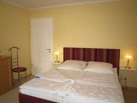 Das komfortable Bett mit zwei getrennten Matratzen und hoher Einstiegshöhe im großzügigen Schlafzimmer, in dem sich auch ein zweiter Flachbild-TV befindet