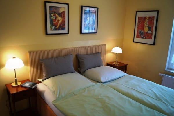 Das Schlafzimmer mit großem Bett mit zwei Matratzen und hoher Einstiegshöhe