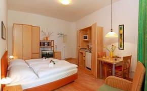 Der Wohnraum mit Flat TV ist in warmen Farben gehalten und mit einem hochwertigen Boxspringbett ausgestattet.  Das Badezimmer ist mit Dusche und WC ausgestattet.
