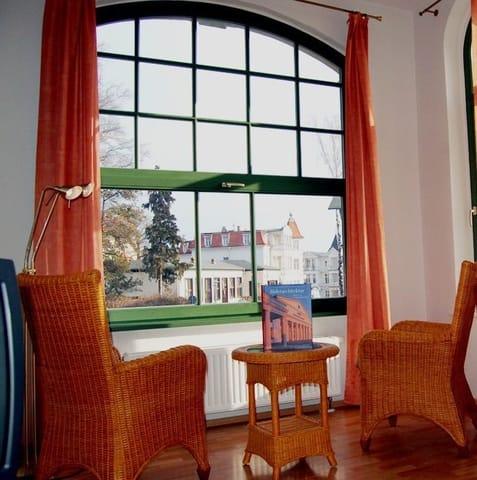 Das Wohnzimmer besitzt nicht nur eine gemütliche Polstersitzecke zum Entspannen  – auch die Loggia ist ein erstklassiger Ort zum Ausruhen. In den bequemen Relaxstühlen können Sie sich einem spannen.