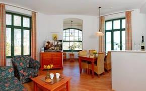 Das Wohnzimmer besitzt nicht nur eine gemütliche Polstersitzecke zum Entspannen – auch die Loggia ist ein erstklassiger Ort zum Ausruhen. Die Sonne genießen Sie auf den Balkonen.