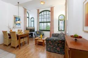 Der großzügige Wohnraum ist in warmen mediterranen Farben gehalten, die gemütliche Polstersitzecke mit Flat TV lädt zum Erholen und Ausspannen ein.