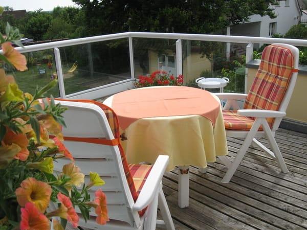 Die Süd- West- Dachterrasse mit Sonnenschirm und Liegen.Die Glasverkleidung lässt den Blick auf den Garten frei.