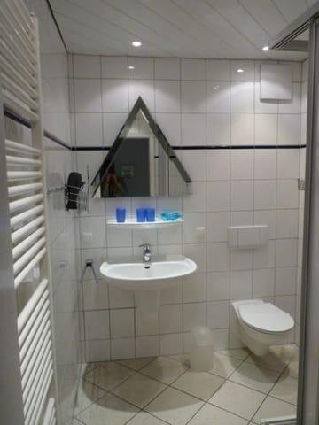 Bad mit Dusche und WC,  Kosmetikspiegel und Fön