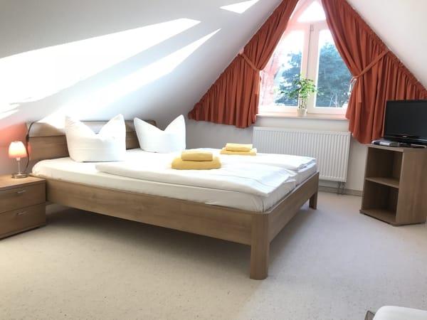 großes , sehr schönes Schlafzimmer im Dachgeschoss mit einem großen Doppelbett und einem zusätzlichen Einzelbett , SAT-TV , erreichbar durch Treppe