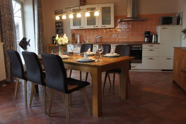 Großer Esstisch und komfortabel mit Markengeräten ausgestattete Küchenzeile