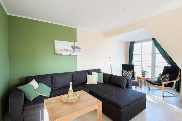 Wohnraum mit gemütlicher Sitzecke sowie zwei Schwingsessel